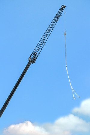 telescopic: Telescopic mobile crane arm with ball and chain.  Blue sky and soft fuzzy clouds.