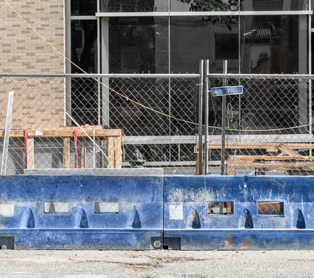 building a chain: Blue construction barrier and chain link fence in front of new commercial building. Wooden frames and pallets, brick structure with large window.