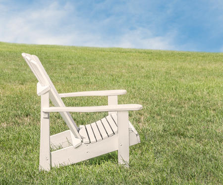 adirondack: White wooden adirondack chair on green grassy field.  Blue sky and clouds background. Copy space.