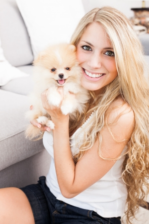 pomeranian: young woman playing with her tinny dog at home Stock Photo