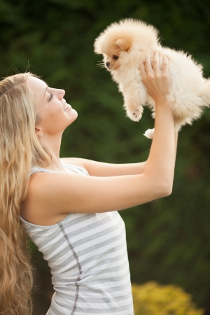 young woman playing with her tinny dog at home photo