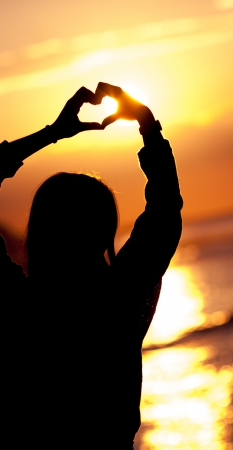 women silhouette makes heart shape sunset photo