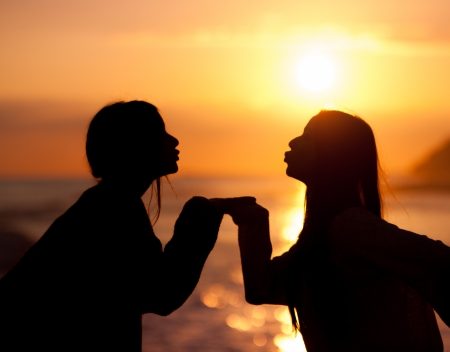 silhouette two young beautiful friends kiss on sunset photo