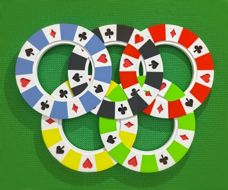 closeup focused on black, yellow, green, blue and red poker chips situated in olympic circles on table photo