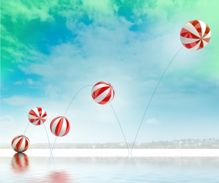 five jumping white red striped inflatable balls with beach and sea waterreflection cityscape background Stock Photo