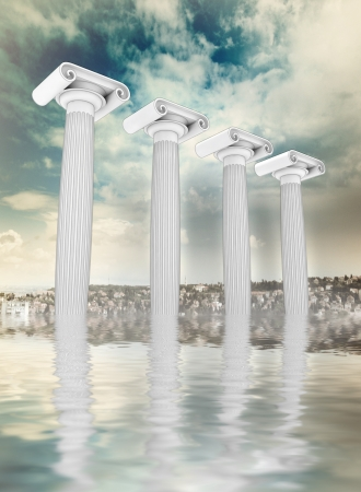 sunken: four column in the ancient Greek Ionian style in row sunken on cityscape backgroung with blue cloudy sky  Stock Photo