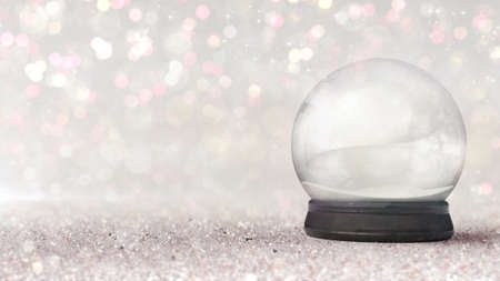 Magic snow globe as christmas classical decoration on bright bokeh background.