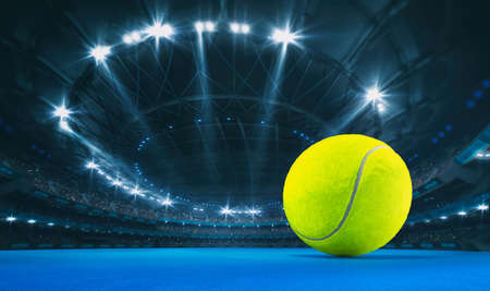 Magnificent tennis arena with a tennis ball on a blue artificial floor with spectators on the grandstand. Professional world sport 3D illustration background. Banco de Imagens