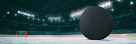 Sport indoor ice hockey arena with black puck on the ice rink as widescreen background. Digital 3D illustration of sport building interior. Фото со стока