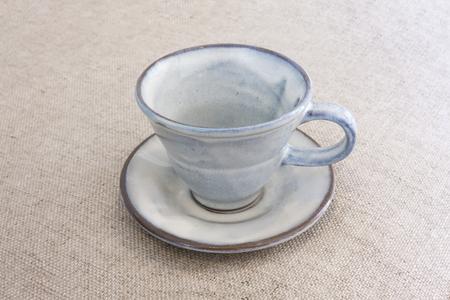 brownish: indigo blue empty coffee cup on brownish background
