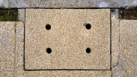 dirtiness: manhole cover of sanitary sewer drainage pipe under footpath Stock Photo