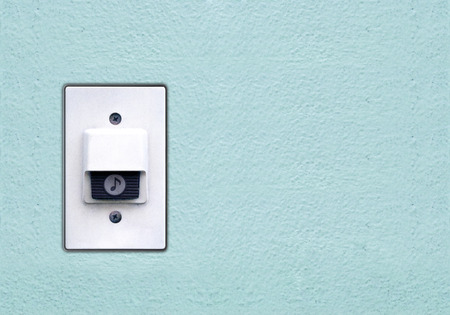 buzzer: Doorbell or buzzer on mounted on green wall
