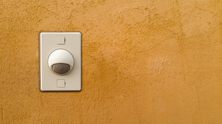 buzzer: Doorbell or buzzer on mounted on orange wall Stock Photo