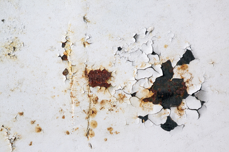 Old rusty metal surface with remnants of white colors