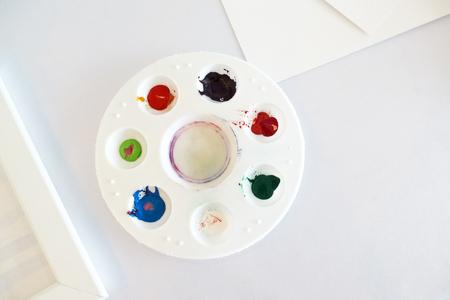 Multicolored watercolor in a round white plastic tray.