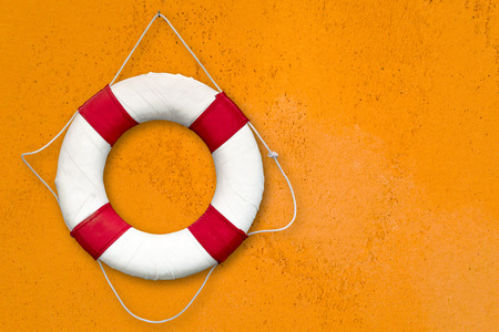 Red and white life buoy on the orange background. 版權商用圖片