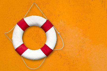 Rote und weiße Rettungsboje auf dem orangefarbenen Hintergrund. Standard-Bild