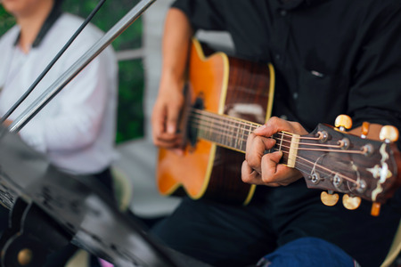 A Mens hand playing guitar with friends during the live performance on stage. Focus selection Stock Photo