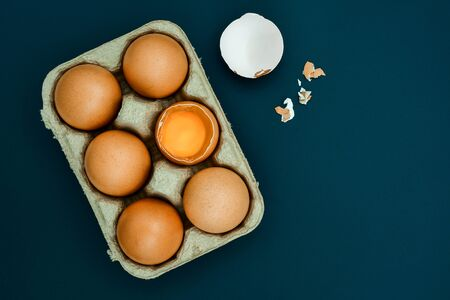 White egg and egg yolk in egg box on Light gray background, top view. With copy area