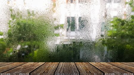 The small raindrops on the window glass in the rainy season intersect with the green backdrop. plank table surface. Free place for creativity. Background.