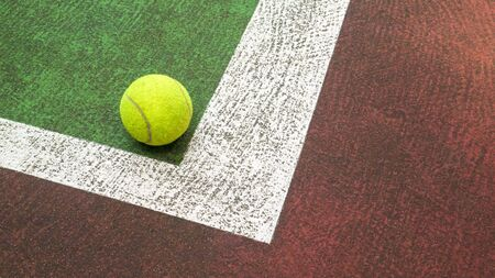 Yellow tennis ball hitting the sidelines on an green and orange artificial tennis court, sport background Banco de Imagens - 131894430