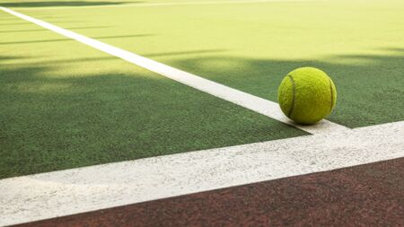 Yellow tennis ball hitting the sidelines on an green and orange artificial tennis court in the afternoon sun. sport background Banco de Imagens - 131894068
