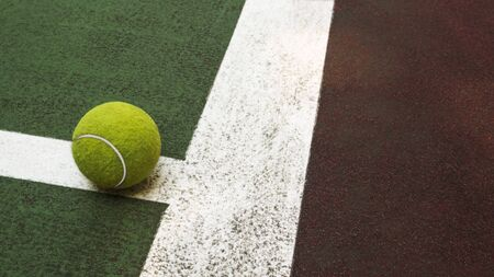 Yellow tennis ball hitting the sidelines on an green and orange artificial tennis court, sport background