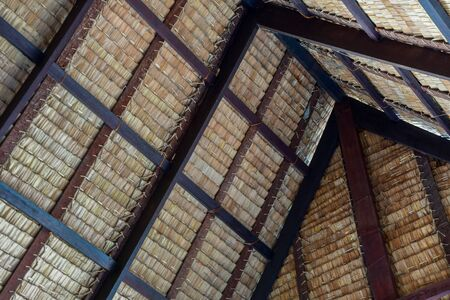 Traditional swiss thatch roof from the inside. Piece of a tap thatching that made from strips of Nipa leaves, nature leafs texture background. Banco de Imagens