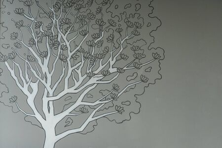 The abstract nature design of the tree with a black-gray picture of trunks and twigs in the foreground and gray birch stripes on gray walls.