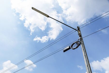 Street lamps and wires with line cables, transformers and phone lines on old electricity pillar or Utility pole at beside road