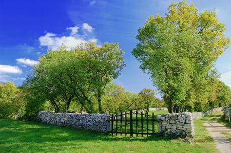 quietness: Closed wooden gate in a stone wall Stock Photo