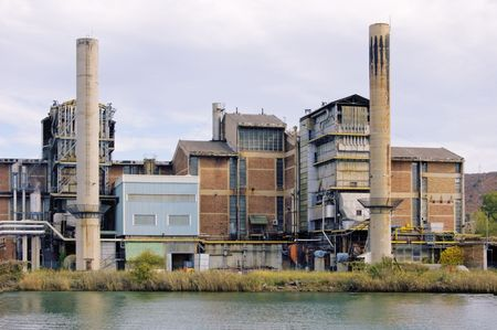 Factory with two chimneys on a river Stock Photo