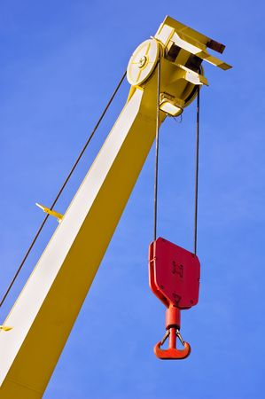 Yellow crane with red hook against blue sky
