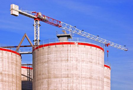 cylindrical: Silos under construction with crane against a blue sky Stock Photo