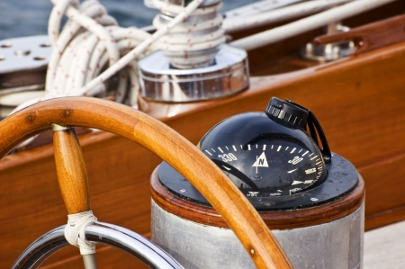 Rudder and compass on a wooden boat Stock Photo