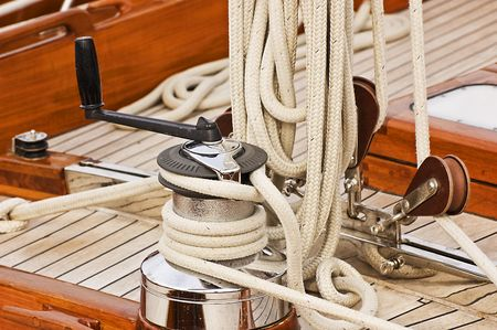 Winch with crank, pulleys and rope on a sailing boat Stock Photo