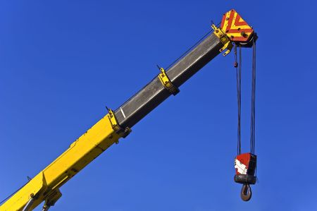 Crane with hook against blue sky