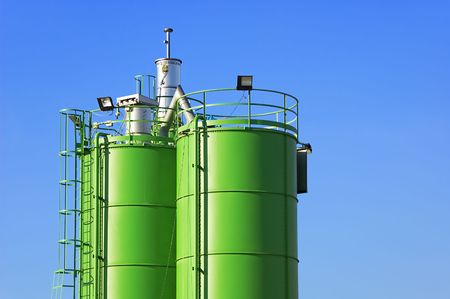 Two green silos agaist blue sky in a construction site
