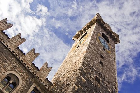 crenelation: Medieval tower with clock of a caste in Trento (Italy) Stock Photo