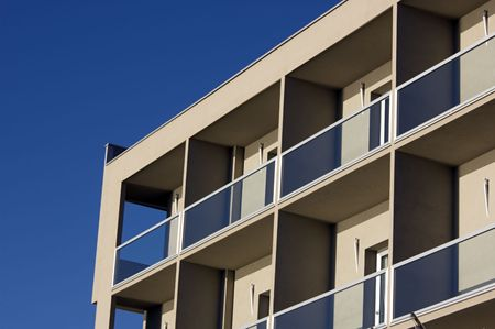 glass partition: Front of building with terraces against a blue sky