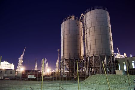 cylindrical: Construction site with silos by night Stock Photo