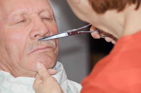 Woman shaves mustache in a barber shop photo