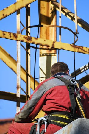 Workman with overalls and harness in a construction site