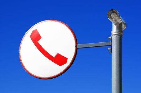roundish: Round sign with telephone against blue sky