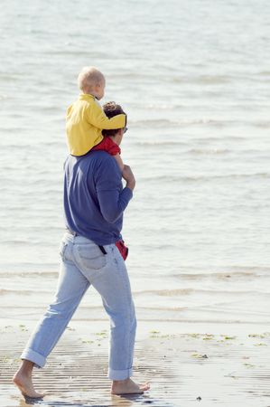 Father with son on his shoulders walking barefoot on the shore-line Stock Photo