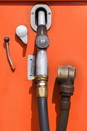gallons: Obsolete orange fuel pump at a gas station