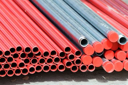 Stack of metallic pipes in a construction site Stock Photo