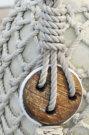 Close-up of an old block on a sailboat with a bumper covered by a rope net in background
