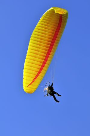 Man with a yellow paraglider flying in the sky