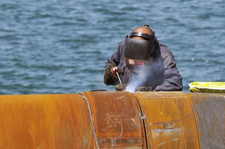 Worker welding two big pipes in a harbour Stock Photo